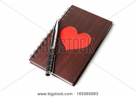 wooden texture notebook with red heart and pen on white background.