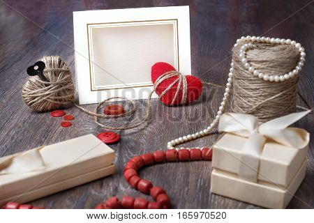 Valentines day photo frame or greeting card and handmade hearts over wooden table. copy space