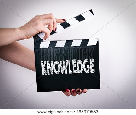 Knowledge. Female hands holding movie clapper. Gray background