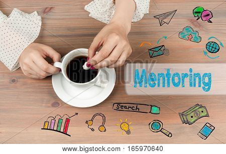 Mentoring. Coffee cup top view on wooden table background.