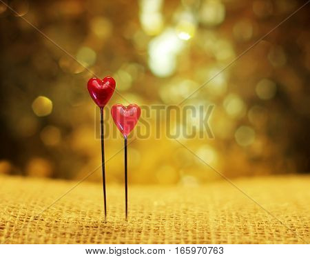 two small pins hearts on festive shimmering background