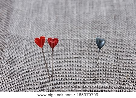 Two red little hearts and one blue on a background of linen fabric