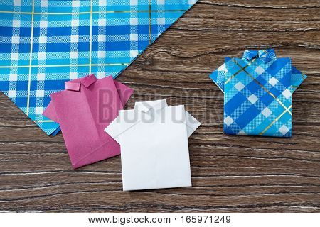 Gift For Father's Day Background, Copy Space. The Child Makes A Gift Of Origami Paper Shirt. Made By