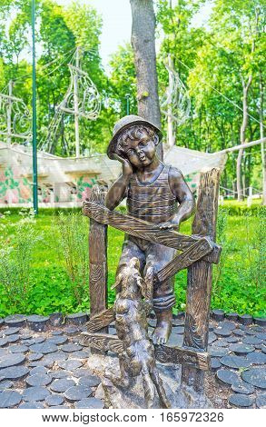 KHARKOV UKRAINE - MAY 20 2016: The bronze sculpture of a ittle boy dreaming at the fence with his dog and white magic ship sails on the lawn behind him Gorky Park on May 20 in Kharkov.