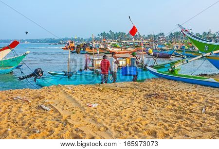 HIKKADUWA SRI LANKA - DECEMBER 5 2016: The fishermen unload their catch weigh the fish and moor the boat at the old fishing harbor on December 5 in Hikkaduwa.