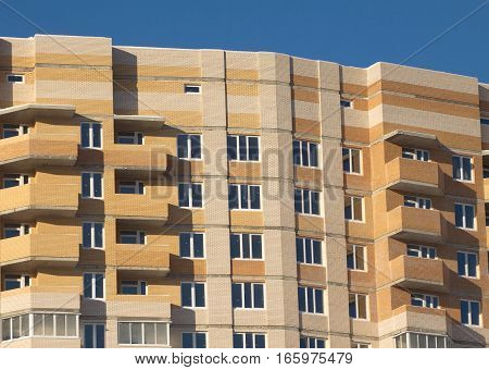 Top section of construction brick building over clear blue sky