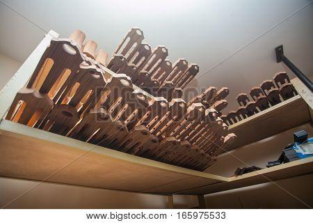 many vultures for guitars lie on shelf at workshop.