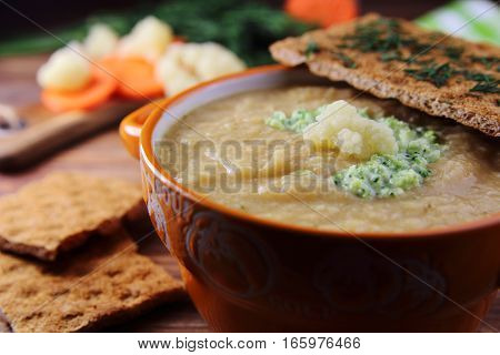 cream soup of cauliflower and carrots with bread and dill