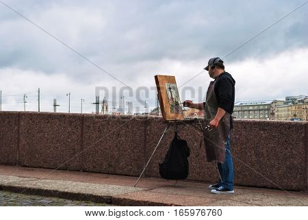 SAINT PETERSBURG RUSSIA may 14: the Artist with his easel draws the Rostral column on the spit of Vasilievsky island 14 may 2016 in Saint-Petersburg.