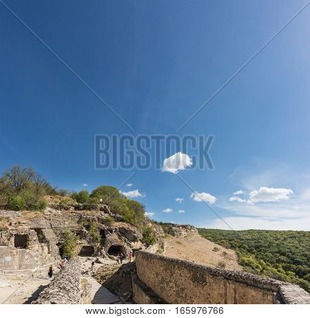 BAKHCHISARAY REPUBLIC of CRIMEA RUSSIA - SEPTEMBER 13.2016: Tourists are considering monastic cells in the rock. Over the southern gate of the medieval town-fortress Chufut-Kale