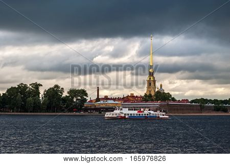 Motor ship sailing on the river Neva on a background of the fortress in a gray cloudy day in Saint-Petersburg.