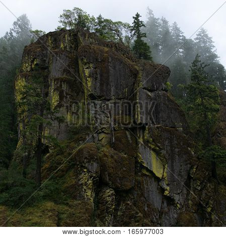 A large rock formation on the banks of the North Umpqua River in Douglas County in Western Oregon on a foggy summer day.