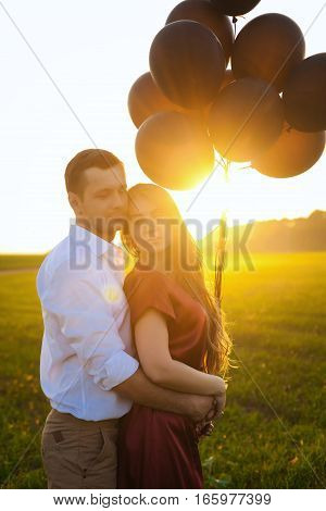 guy in white shirt and girl in red dress hugging at sunset. In their hands are black balloons
