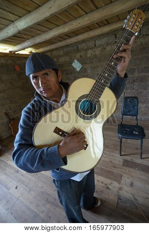 July 22 2016 San Bartolome Ecuador: an indigenous luthier holds up an finished guitar in his small rural shop