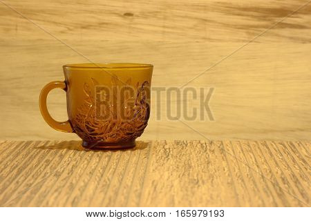 Teacup shot against a wooden background on a tiled surface