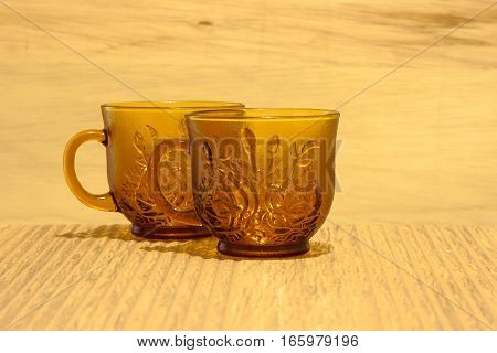 Teacups shot against a wooden background on a tiled surface