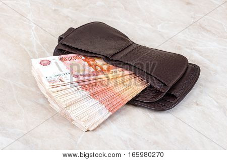 Wallet open with a heap of five thousands russian rubles sticking out