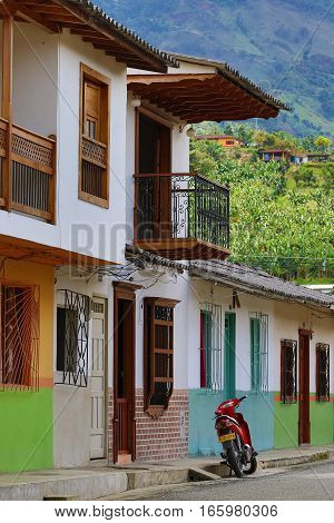 September 30 2016 El Jardin Colombia: a motorbike is parked in the front of the colourful buildings of the coffee production town. Because of the high road fees for cars motorbikes are very popular in Colombia.