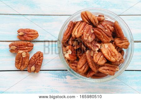 Pecans (Carya illinoinensis) on a blue table. Walnuts hickory nuts