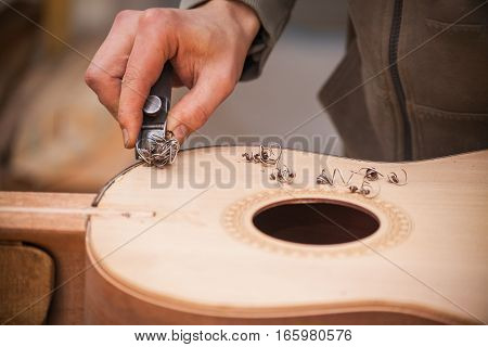 Serious professional guitar-maker working with unfinished guitar at workshop.