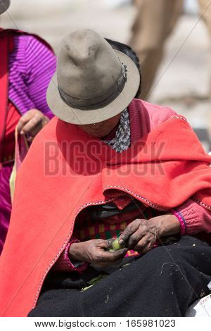 July 24 2016 Alausi Ecuador: indigenous man wearing a red poncho and felt hat in the local market