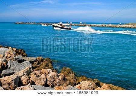 A boat traveling along a channel rocks in foreground