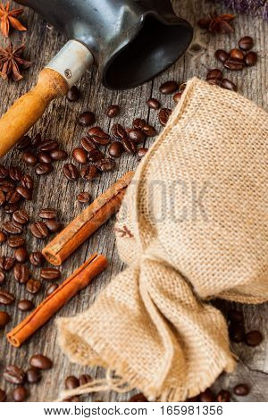 Roasted coffee beans with burlap sac, Cezve, on old weathered wood, cinnamon. Vintage, rustic background . Place for writing text