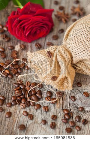 Roasted coffee beans, red rose on a brown wooden background with coarse roughly woven burlap, grunge texture. Place for your text