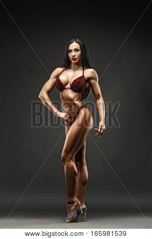Strong and muscular sports girl in bikini posing against camera in studio