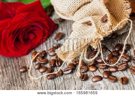 Roasted coffee beans, fresh red rose, coarse burlap sac on old wooden table. Vintage still life.