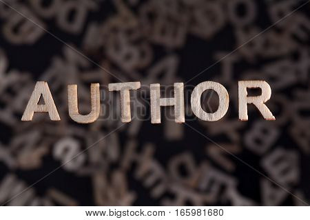Author wooden letters created in wood floating above random letters below out of focus on a black background
