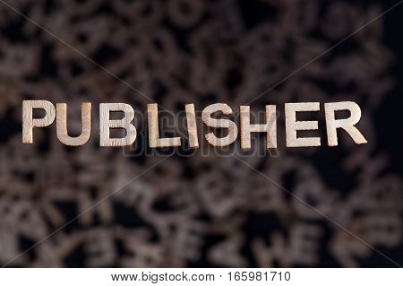 Publisher wooden letters created in wood floating above random letters below out of focus on a black background