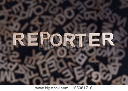 Reporter wooden letters created in wood floating above random letters below out of focus on a black background