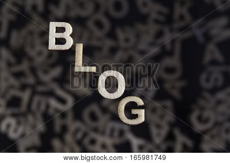 Blog wooden letters text on an angle created in wood floating above random letters below out of focus on a black background