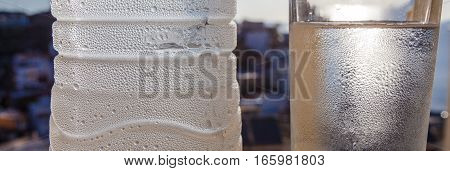 Water bottle with drops and glass on the city and sea background and the sun