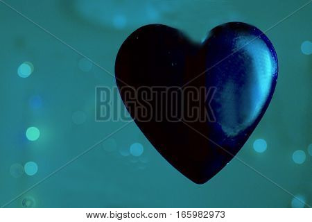 Blue transparent heart on color background. No people