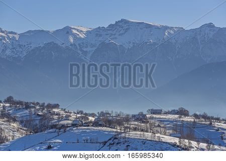 Rural landscape with traditional Romanian village at the base of Bucegi mountains on a sunny cold winter morning in Pestera Brasov county Transylvania region Romania.