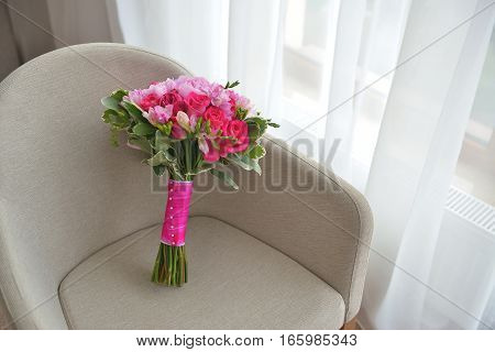 Beautiful Wedding bridal pink and violet flovers piones Bouquet on beige chair. Background, floristic composition