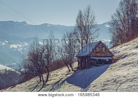 Deserted weathered wooden ramshackle. Winter rural landscape with old rustic wooden cowshed in Pestera village Rucar-Bran pass Brasov county Romania.