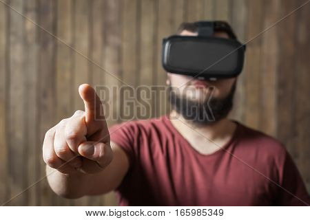 Bearded man with virtual reality glasses press finger on the wooden background