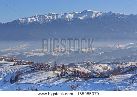 Magnificent rural view with the snowy Rucar-Bran pass in the valley of Bucegi mountains on a cold winter day Pestera village Brasov county Transylvania region Romania.