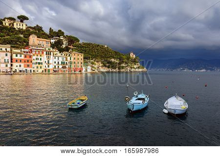 Stormy sky and small boats in sea bay of Portofino town. Portofino is small fishing town in Liguria district in Italy.