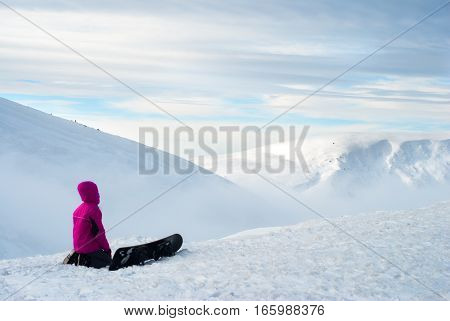 girl sitting with a snowboard on top of mountain