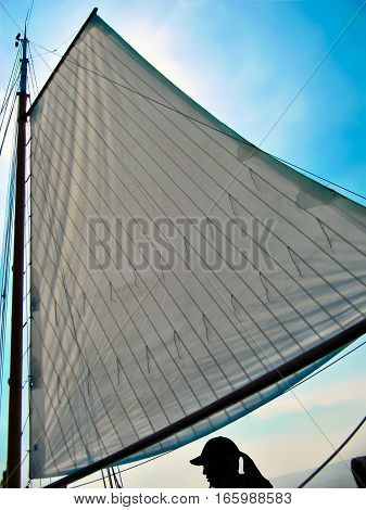 A big Sail with a blue sky, a black woman silhouette is sailing