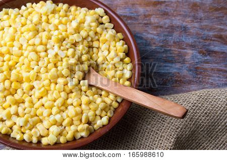 Bowl Of Frozen Corn With A Wooden Spoon