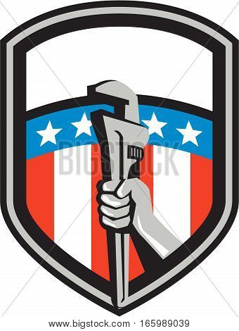 Illustration of a plumber hand holding adjustable pipe wrench viewed from the side set inside shield crest with usa american stars and stripes flag in the background done in retro style.