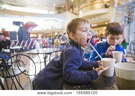 kids in a cafe drinking hot chocolate. funny child drinks of cocoa through a straw.