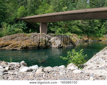 A bridge crosses the North Umqua River and its rugged and rocky banks at the Swiftwater Recreation Site in Douglas County in Western Oregon on a summer day.