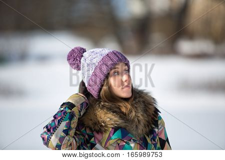 Beautiful young woman in bright knitted cap in winter park