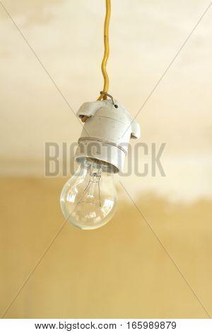 Electric bulb in white ceramic cartridge hangs on yellow cord